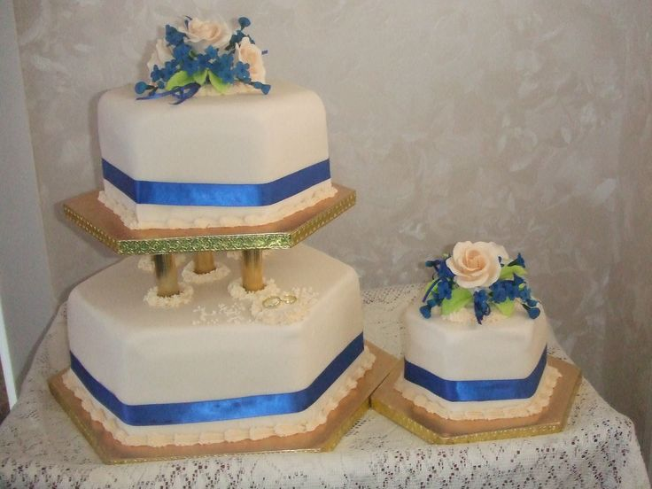 """This hexagon 3 tier cakes was made for  the couple as they are bee suppliers , -this is why the shape was chosen. the bottom cake is fruit, the top tier is chocolate and the little cake is  a fruit  Gluten free cake. the cake is covered in Celebration cream -Renshaws with royal blue satin ribbon with cream roses and royal blue filler flowers    Cakes For All Occasions (Cake Talk with Margaret """") Mosgiel Otago New Zealand website: www.icedcakes.co.nz"""