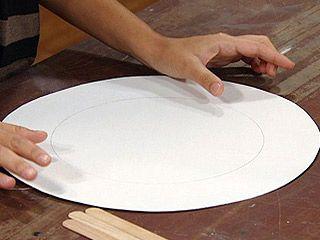 Cortar un círculo de cartón 6 cm más grande que el espejo.
