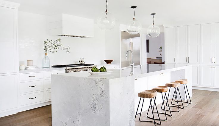 A gorgeous and bright marble kitchen with wood and iron stools