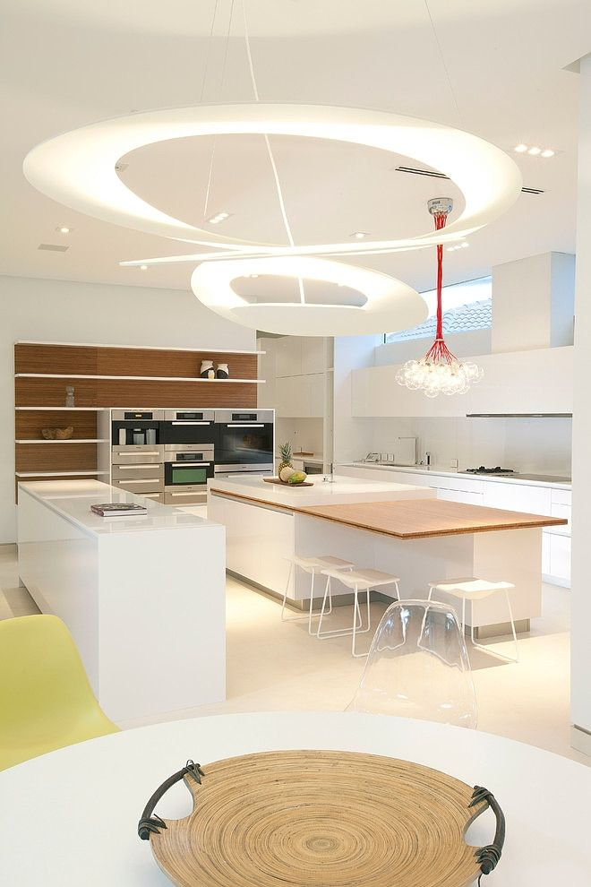 another view of the white, minimalist kitchen with the island.  we like the wood elements incorporated as well. #artemide #lightborn  www.artemide-obchod.cz