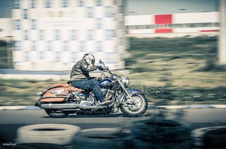 Ulyanovsk, Russia - August 19, 2017. A motorcycle racer on a classical motorcycle trains on a sports track. Motion blur.