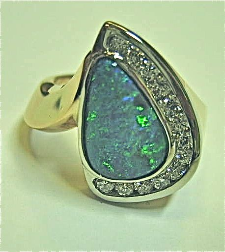 Custom designed fashion ring by Designs In Gems containing a bezel set Lighting Ridge black opal and channel set round full cut diamonds in a 14k yellow gold mounting.