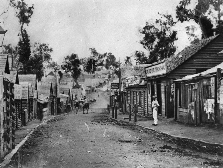 View along Mary Street, Gympie, ca. 1870 - View along an unsealed Mary Street, Gympie. Shops and buildings of timber construction with shingle rooves line both sides of the street.