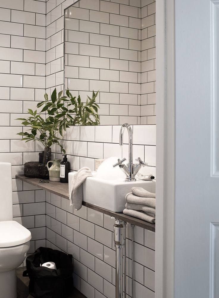 Tiles with dark grouting. Tap to side of sink to maximise depth from wall. Warm coloured shelf.