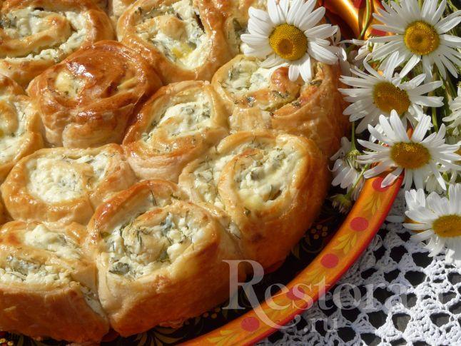 Хочу поделиться рецептом закусочного пирога. Пирог из слоёного теста с фетой, получается вкусный и сытный, его можно легко разобрать на порционные булочки-завитушки. Такой пирог можно взять с собой на пикник и устроить лёгкий перекус.