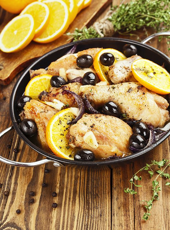 Chicken with oranges and olives in a frying panChicken with oranges and olives in a frying pan