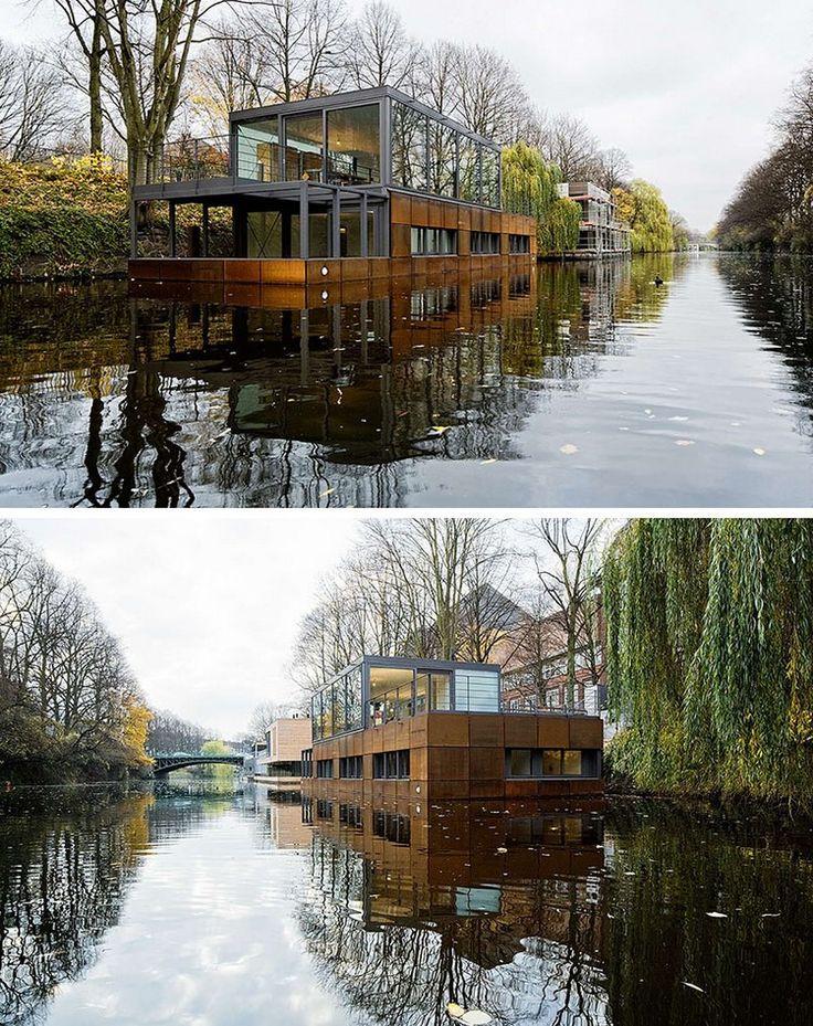 maison sur l'eau avec parement en bois et grandes baies vitrées, paysage naturel…