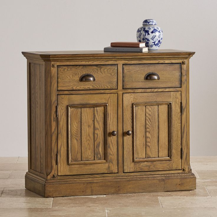 Pleasing, solid oak small sideboard with Manor Houses decorative dowelling and darker-oak finish. Use for storage in the living room, dining room, or kitchen. Two flat-fronted drawers with dovetail joints sit above a shelved cupboard for holding table linen or board games.