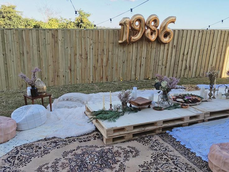 DIY boho style backyard 30th birthday party  Bohemian pallet table lots of candles and platters - helium 1986 balloons  See this Instagram photo by @covetandgather • 193 likes