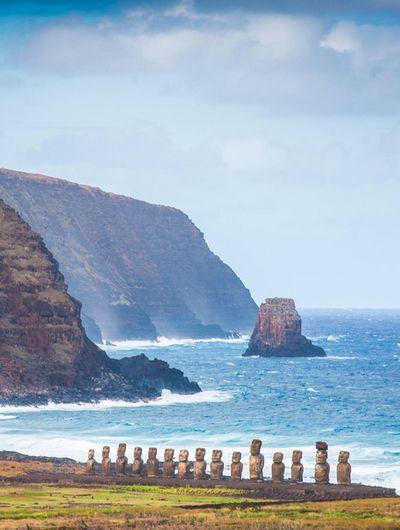 Statues (Moaïs) dressées dos à la mer, faisant face aux habitations de l'île de Pâques installées au pied de la plateforme