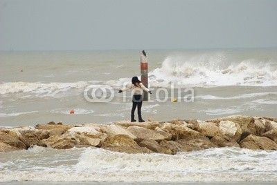 Sea during the winter season and girl breathing the fresh air on the rocks