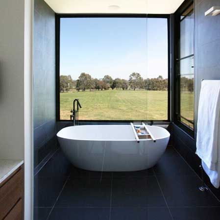 black tiles, timber joinery, freestanding bath, exterior views in Kyneton by JOH Architects Melbourne