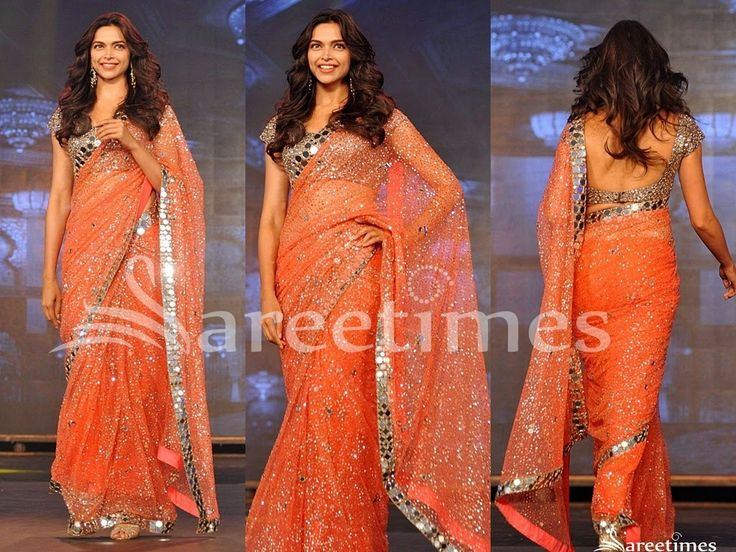 Bollywood actress Deepika Padukone walked on ramp at an event. She looked beautiful in orange embroidery net saree. Silver embroidered sequins buttes and mirrors highlighted on it with mirror work border. Paired with embroidered mirror short sleeves saree blouse for back.