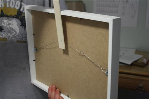 insert a screw through a clean paint stirrer, until it just barely passes through. Hang picture on the screw, place against the wall where you want it, then carefully remove picture while holding the paint stirrer still. Press stirrer against wall, and screw will make a mark where the nail should go.