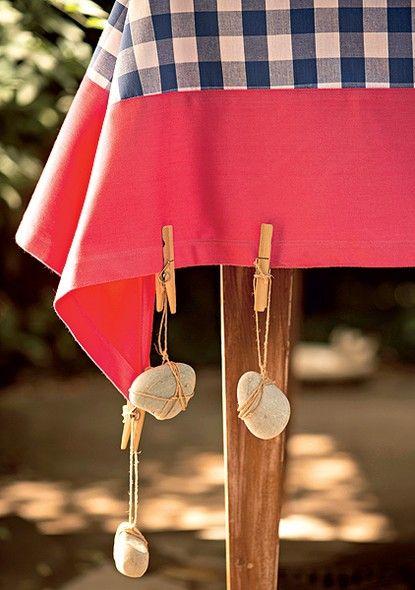 Os pesos de toalha feitos com seixos dão mais bossa à mesa. Amarre as pedras com um barbante de ráfia e prenda o fio em um pregador de roupas. Não se preocupe em fazer todo certinho: o efeito emaranhado é bem-vindo.