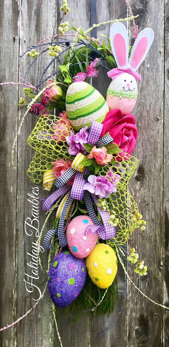 """Bunny Egg Moss Grapevine Swag Measurements X-Large 42"""" Length 18"""" Width Designed on a moss grapevine swag base. Accented with long needle of Spring blooms of green, lavender and pink buds. Large seven loop bow..lime green chicken wire, lavender gingham, Houndstooth and"""