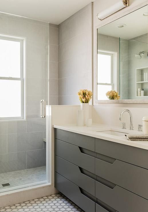 Modern gray bathroom features an ivory full length mirror over a modern gray washstand with drawers topped with off white quartz alongside a hex tiled floor.