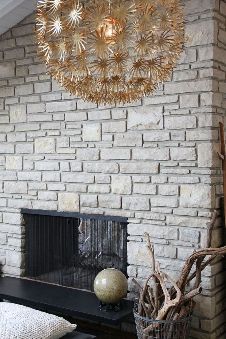 A pendant light in the foreground with a stone wall and fireplace in the background.