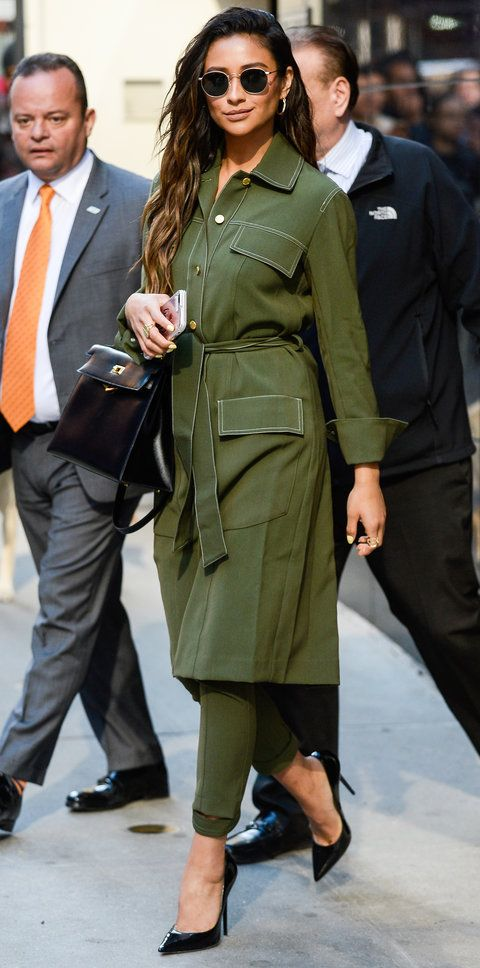 Coat or dress? Whichever it is, Shay Mitchell layered it over matching army green skinnies for a utilitarian-chic look. Of course, it wouldn't be a Shay Mitchell outfit without her signature pumps and matching black accessories: a top handle lady bag, retro sunglasses, and glimmering jewelry.