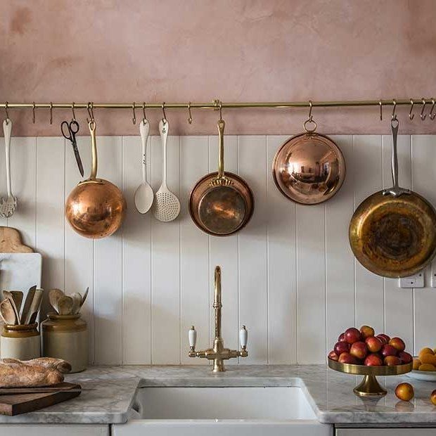 Ditch the junk drawer... A pink plaster wall and brass kitchen rack accent a white-tiled kitchen by Jersey Ice Cream Co.