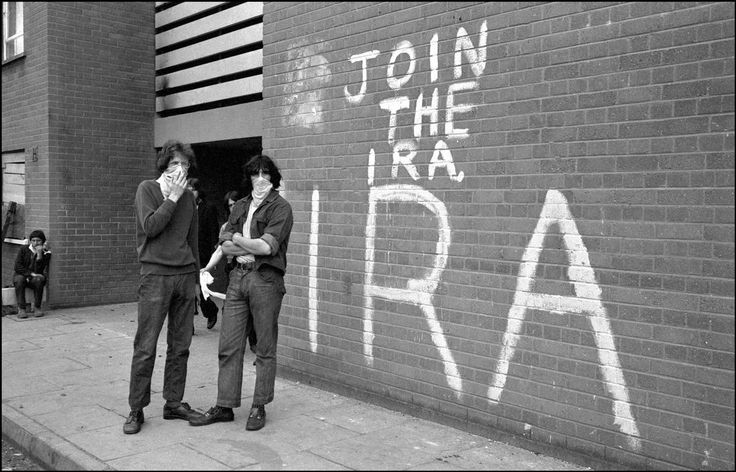 Masked men in front of wall graffiti exhorting people to join the IRA. Derry, Northern Ireland, 1971. Photo by Ian Berry