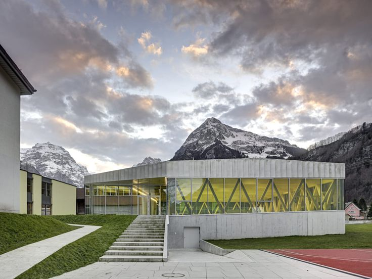 The new Sports Hall neighbors the two existing school buildings and introduces sports, recreation and club life to the polyvalent concept of the area. Three sides of the building are available for play and rest between lessons, becoming the new focal p...