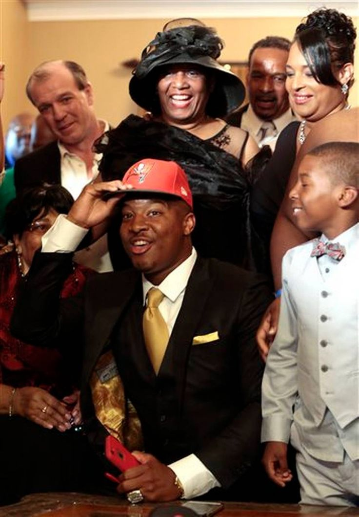 Jameis Winston puts on a Tampa Bay Buccaneers cap as it is announced that he was selected as the number one draft pick while family and friends celebrate, Thursday, April 30, 2015, in Bessemer, Ala.