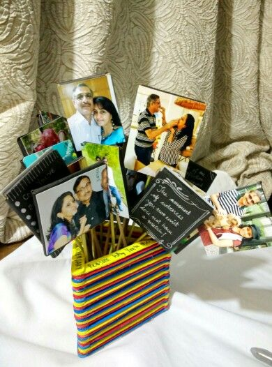 Anniversary gift for mom dad- Bouquet of photographs. A stand made out of hand painted ice cream sticks, and cut pieces of carton inserted in sticks to make tiny placards with pictures stuck on one side and memories associated with them written on the other side.