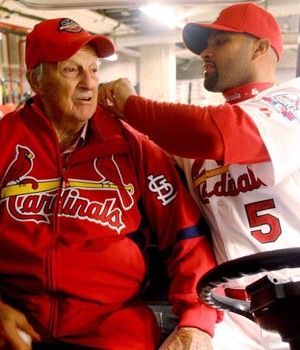 Albert Pujols helps Stan Musial with his Cardinals jacket before the home opener in 2009. (Photo by Chris Lee / clee@post-dispatch.com)