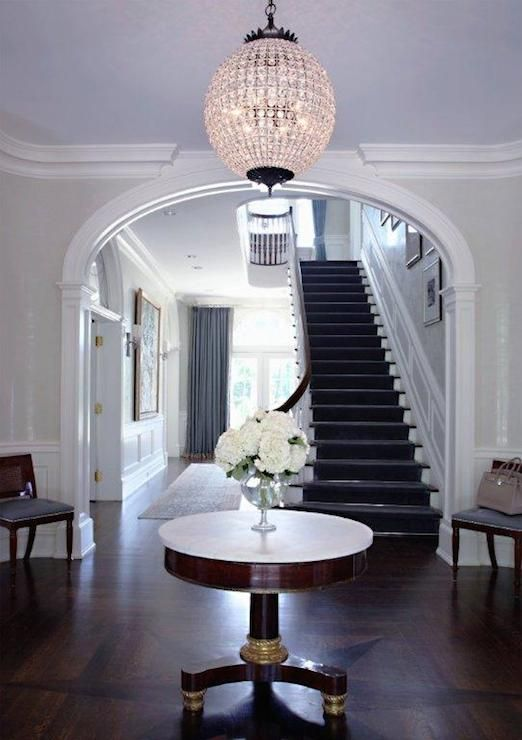 Elegant Foyer With Starburst Parquet Hardwood Floors Framing A Marble Topped Pedestal Table Below Round Crystal Chandelier Highlighted By Pale