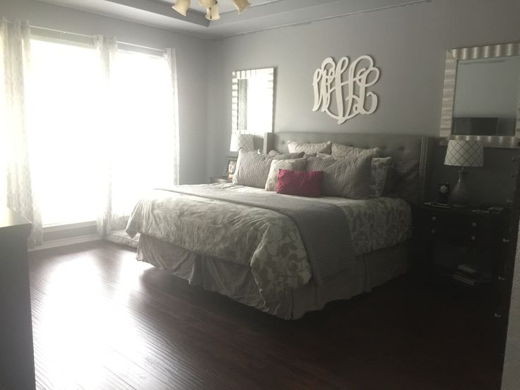 Gray master bedroom, hardwood floors, monogram above bed