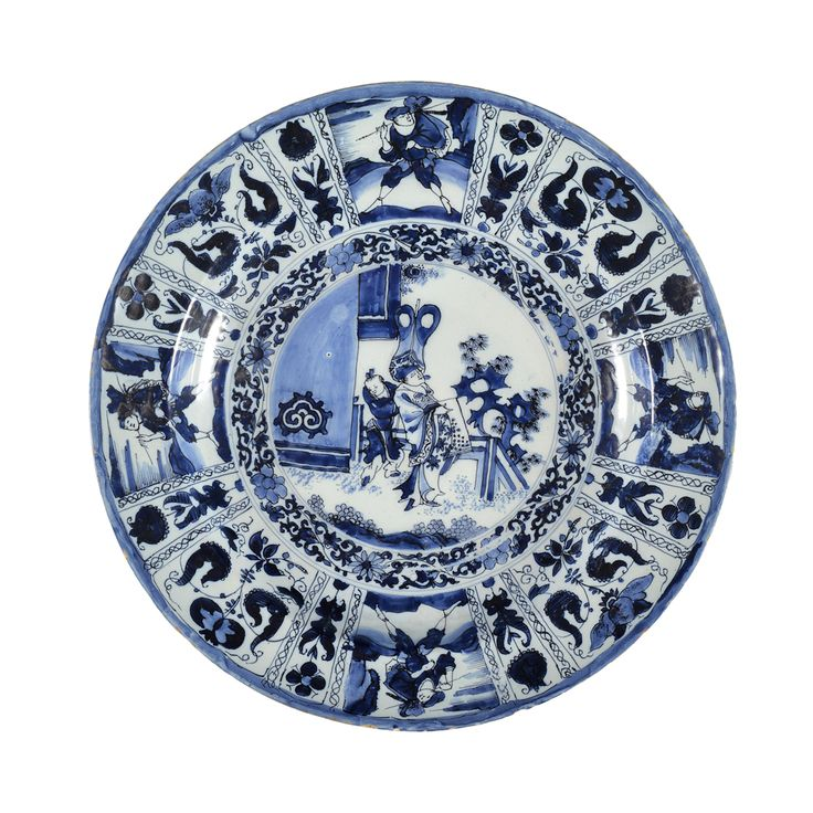 Collection item D1516.     Blue and White 'Kraak'-Style Large Dish     Delft, circa1680 - 1685     Marked SVE in blue for Samuel van Eenhoorn, the owner of De Grieksche A (The Greek A) Factory from 1678 to 1685  Painted in the center with a Chinese dignitary holding a scroll and standing before his