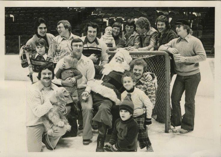 Xmas 1974: Orest Kindrachuk holding a dog, Ross Lonsberry holding his kid, Larry Goodenough, Andre Dupont, Joe Watson, Wayne Stephenson with his kids, Tom Bladon, Don Saleski, Dave Schultz, Bob Clarke and Terry Crisp holding Santa and his kids.