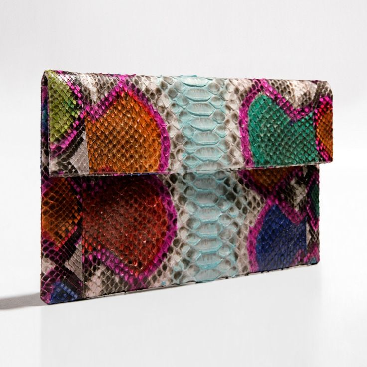 Blue multi coloured python clutch by Verinosa Add a dash of creativity to your outfit with this cheerful multi coloured clutch. An eclectic melting pot of inspiring handmade artful patterns applied on authentic python. The perfect clutch for a unique fabulous eye catching look.Designer Colour: Blue Multi ColouredGenuine Python snakeskin: IndonesiaInterior: Suede lining and debossed designer letteringMagnetic-fastening front flapAvailable with and without removable chain strapDimensions…