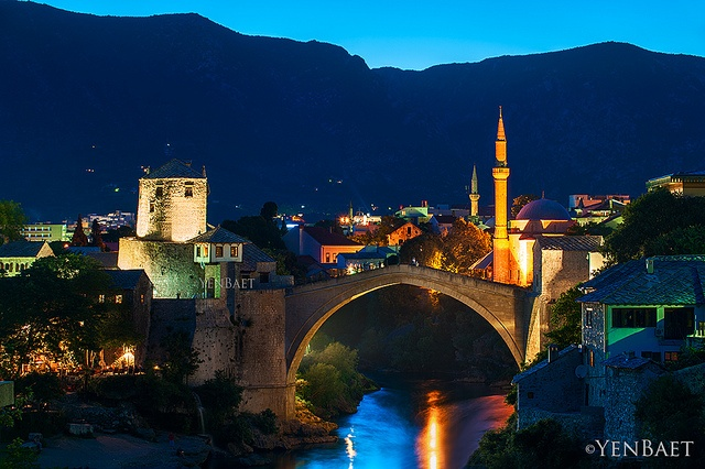 "Mostar, Bosnia & Herzegovina - Twilight at Stari Most - Photo © www.YenBaet.com.  The Stari Most is the most important bridge of Mostar named after the city - Mostar which means ""bridge keeper."" The bridge was attacked with tank fire and more than 60 shells hit the bridge before it collapsed. At the end of the war, UNESCO established an international committee of experts to oversee the design and reconstruction work. The successfully rebuilt bridge opened on July 23, 2004."