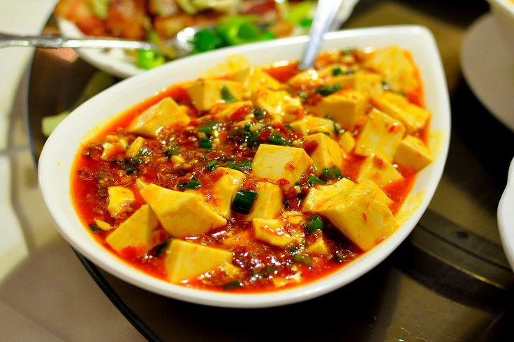 """Classic Mapo tofu. Cubes of super-soft silken tofu -- served in a mind-numbingly hot sauce made from """"doubanjiang"""" (a flavor-packed broad bean paste), """"dou-chi"""" (fermented black beans), freshly ground Szechuan peppercorn powder, sesame oil and light soy sauce. Garnished with minced garlic greens."""