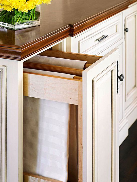 Tablecloth storage hidden in kitchen cupboard.  Part of a slideshow with lots of great kitchen storage ideas.