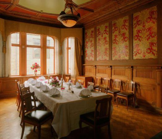 I andre etasje av Apotekergården finner du apoteker Øwres staselige spisestue, nennsomt restaurert og dekket til fest. Det helhetlige designet er typisk for jugendstilen. Foto: Jugendstilsenteret i Ålesund
