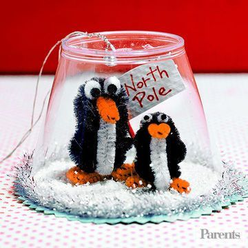 Encase photos, crafty creatures, or holiday trinkets inside a plastic cup to make a nifty tree decoration. What you'll need: 5-ounce plastic cup, tack or pin, ornament string, small bead, colored card stock, pencil, decorative-edge scissors, small paintbrush, white glue, opaque white glitter, 2 thin orange chenille stems, 3 black chenille stems, 1 white chenille stem, black and white felt, 1/8-inch and 1/4-inch hole punches, strong craft glue, scissors, white paper, red tooth...