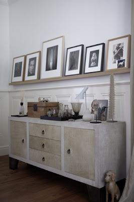 Poner los cuadros en un estante es una buena forma de decorar la habitación así nos libramos de hacer unos cuantos agujeros en la pared.  En esta foto vemos que han usado molduras de color negro también en color madera natural y todas las fotografías llevan un passpartout a medida color blanco.  www.cuadrosdomingo.com