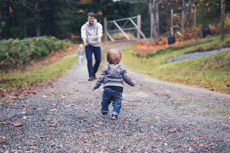 Cute little boy leather jacket and jeans running into daddy's arms.