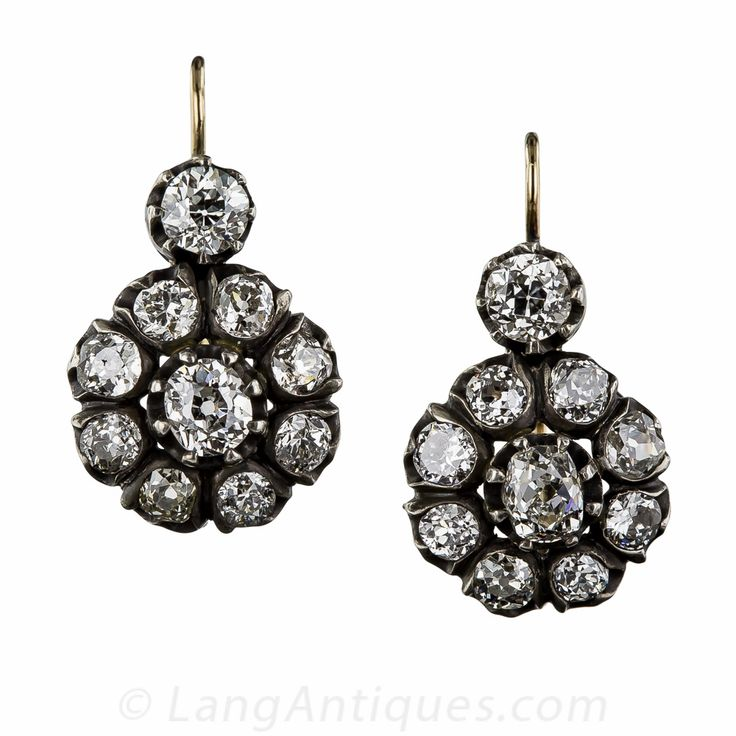 These rare and radiant antique diamond cluster earrings, made by hand in warmly oxidized silver over gold, pack maximum sparkle with 4.25 carats of bright-white and beautiful old mine-cut diamonds. Nineteenth century originals with newer lever-back ear wires. The bottoms measure 9/16 inches in diameter and 3/4 inch from the tippy-top of the top diamond.