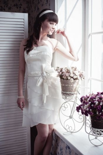 Model 21. A-line short wedding dress -ivory taffeta; -boned bodice, molded cups, layered skirt, draped bow and faux-embellished tie at waist; - concealed zip and lacing fastening along back; - dry clean.