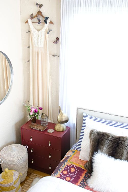 This is the Ikea Rast dresser that we painted and put some hardware on. The woven storage baskets are items we carry. We love these and they are everywhere throughout our small flat for storage and organization which is key for us. The lamp was a vintage find and that's my wedding dress hanging on the wall – it's just too pretty to be put away.