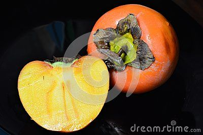 A persimmon, and half of the fruit lay on a black flat plate.