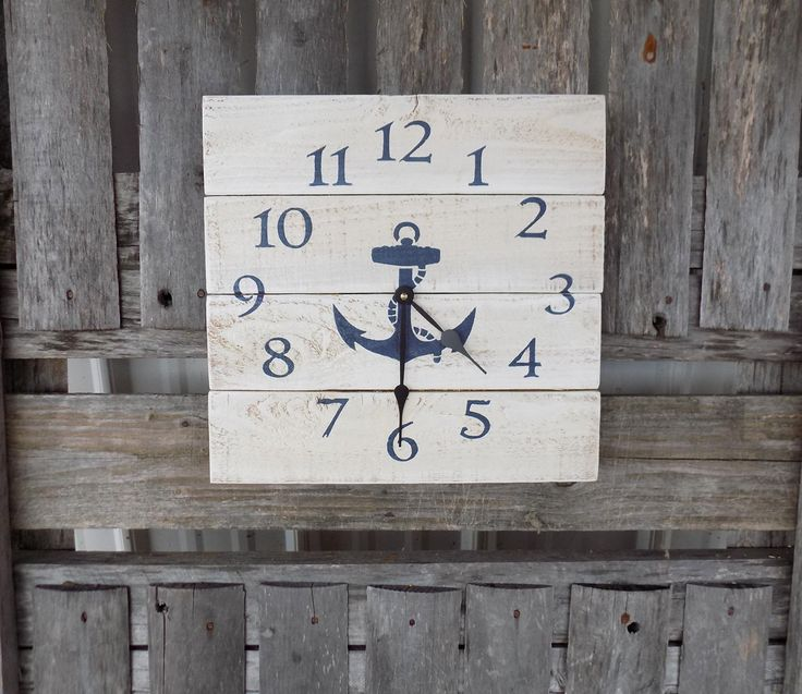 This beach themed clock has been rustically painted an off white, with navy blue numbers and a navy anchor painted in the center. Perfect for a beach or coastal themed room, or even a nautical nursery