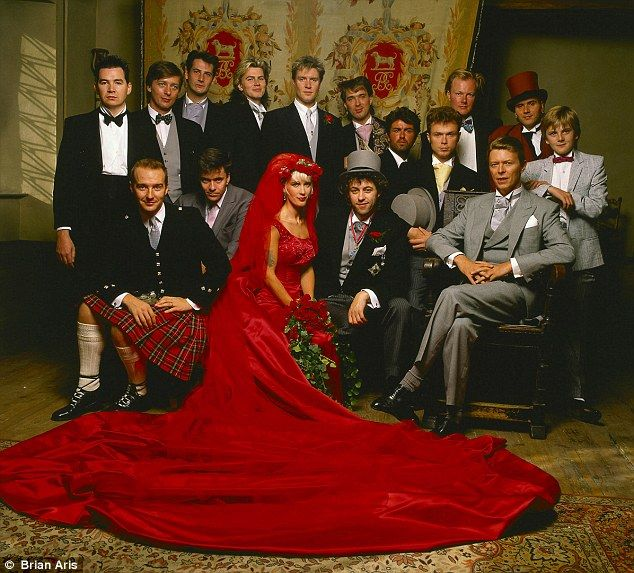Getting wed in red: Paula Yates and Bob Geldof on the day of their marriage in 1986 with his Boomtown Rats bandmates and friends from the world of pop, including Duran Duran and Spandau Ballet. Back row (from left): Johnnie Fingers, Garry Roberts, Tony Hadley, John Taylor, Simon le Bon, Martin Kemp, George Michael, Gary Kemp, Simon Crowe, Steve Norman and the 15-year-old Aled Jones, who sang at the ceremony. Seated (from left): Midge Ure, John Keeble, Paula Yates, Bob Geldof and David Bowie