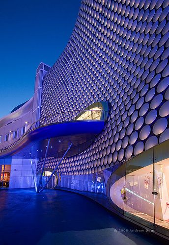 The post modern facade of the Selfridges store in Birmingham is illuminated with blue lights at night. This landmark building was designed by Future Systems and constructed in 2003. (F1702)