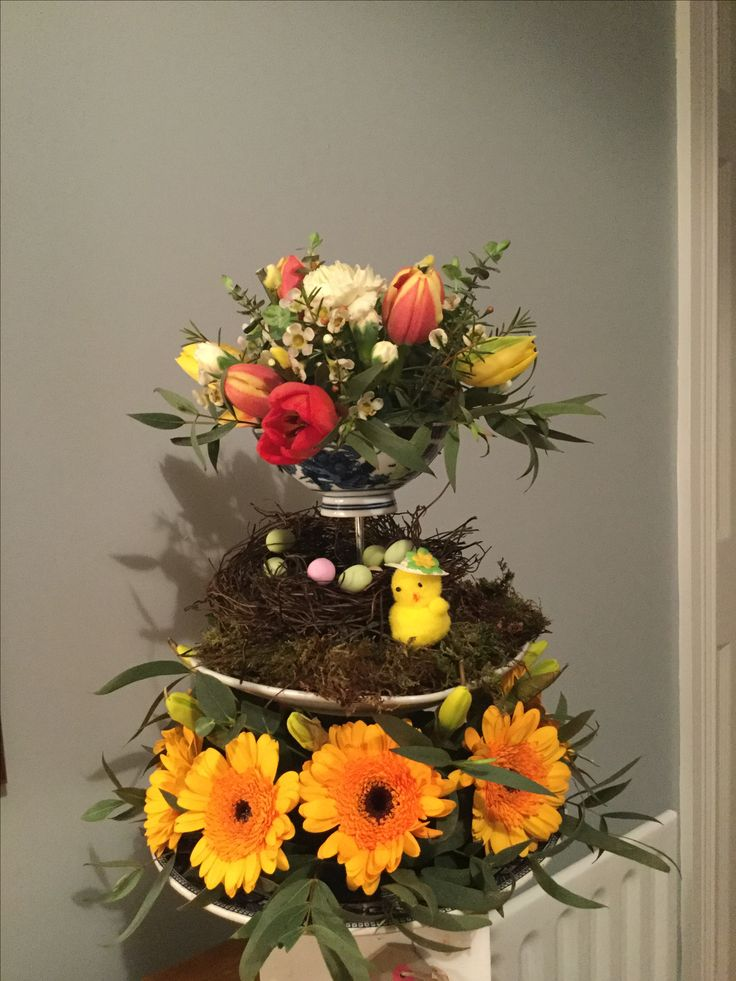 Easter arrangement on a cake stand with tulips, carnations, gerbera, and daffodils.