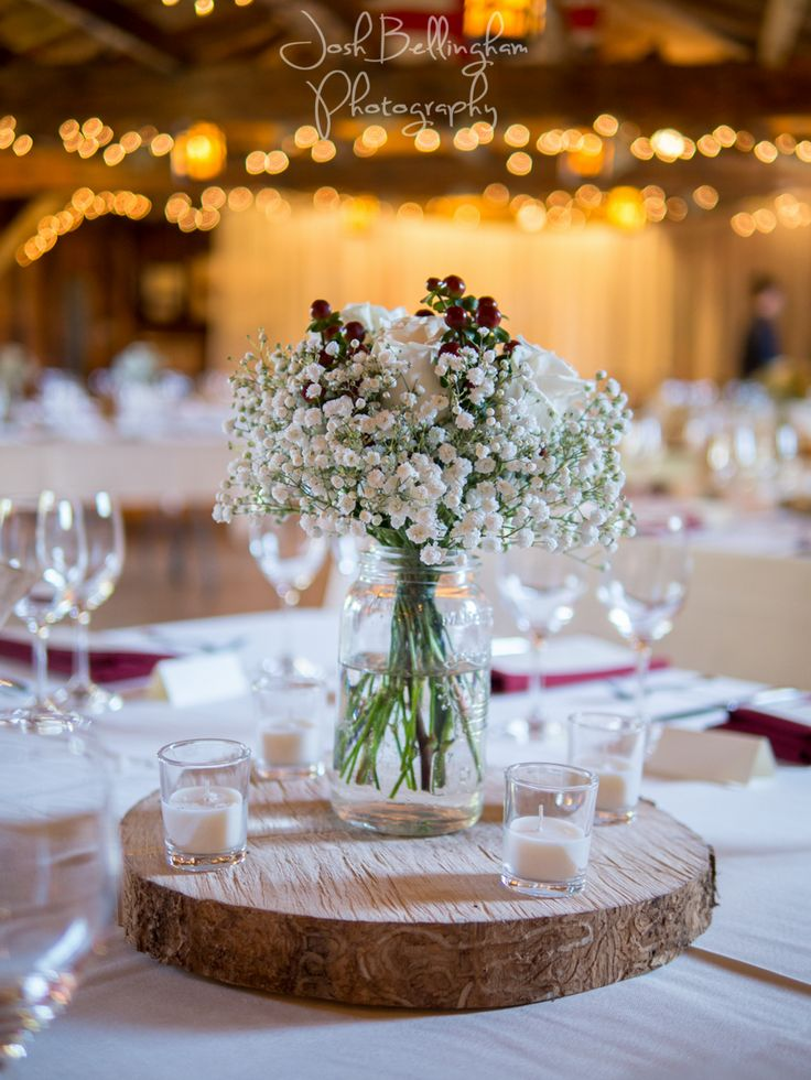 Gorgeous Baby's Breath on Wooden Wedding Centerpieces. I love the sparkling lights in the background with the rustic barn style. Beautiful detail at a Navy Hall wedding in Niagara On The Lake. #JoshBellinghamPhotography